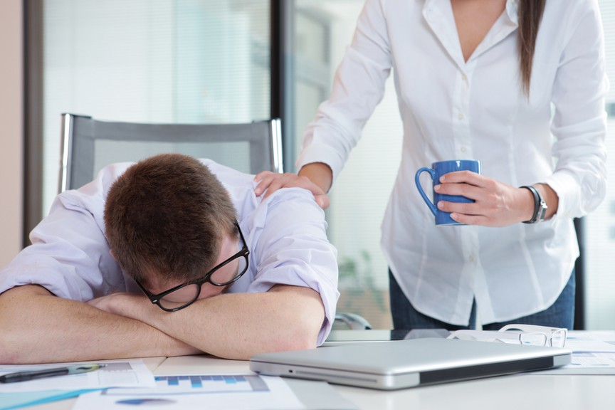 Young office worker is sleeping on the desk colleague gives him a cup of coffee